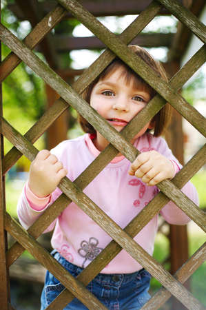 little funny girl behind the fence photo