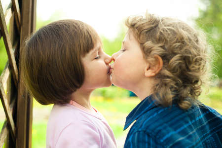 little boy kisses girl photo