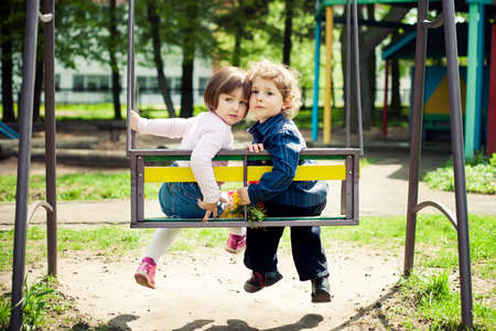 boy and girl on the swings photo