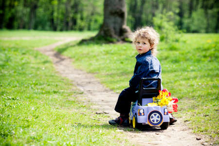 little boy on a toy-car in park photo