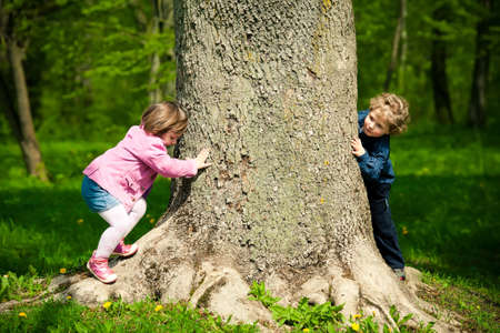 hide and seek: girl and boy playing hide and seek Stock Photo