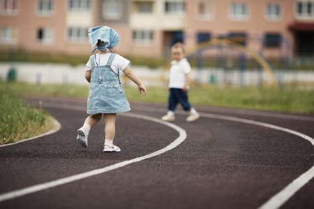 funny little children playing on stadium photo