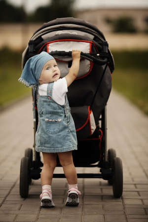 baby stroller: little funny girl with baby carriage outdoors