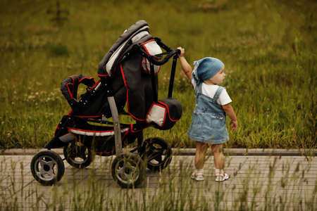 little funny girl with baby carriage outdoors photo