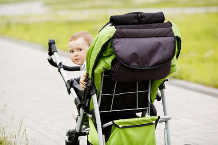 little funny boy with baby carriage outdoors photo