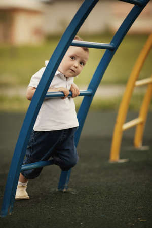 little funny boy plays on playground photo