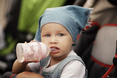 cute baby drinks juice sitting in baby carriage photo