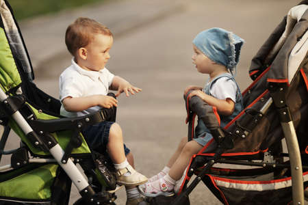 children talking: boy and girl sitting in baby carriages Stock Photo