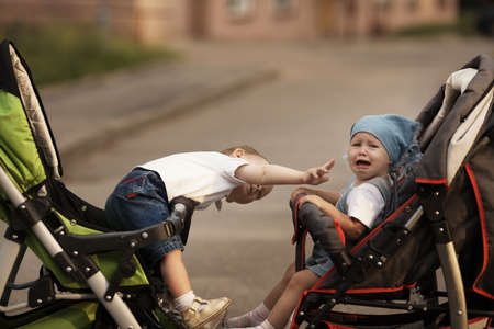 little boy and crying girl with baby carriage photo