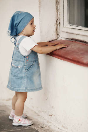 young girl looks to window photo