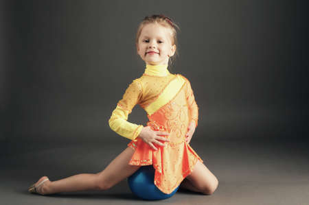 Beautiful girl gymnast with a ball on dark backround photo