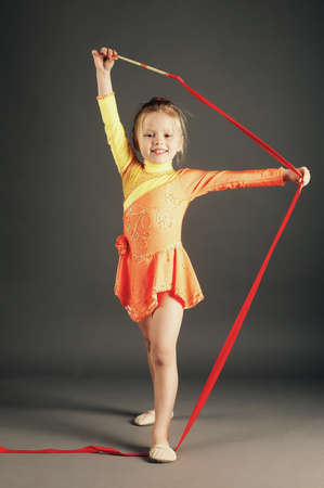 little girl doing rhythmic gymnastics with ribbon