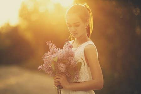 ragazza con bouquet di lillà nei raggi del sole della sera Archivio Fotografico