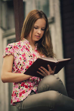 beautiful girl reading book sitting on the porch of  house photo