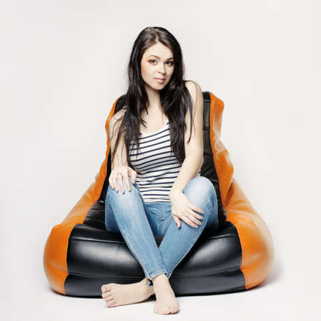 long bean: beautiful girl sitting on beanbag Stock Photo