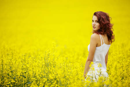 노란색 필드에서 젊은 아름 다운 여자 스톡 콘텐츠