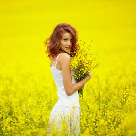young beautiful girl in yellow field 写真素材
