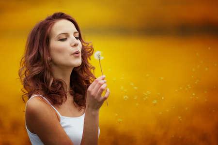blowing dandelion: felice bella donna che soffia dente di leone in campo