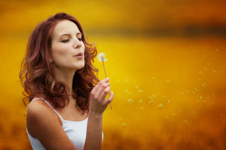 happy beautiful woman blowing dandelion in the field Stock Photo