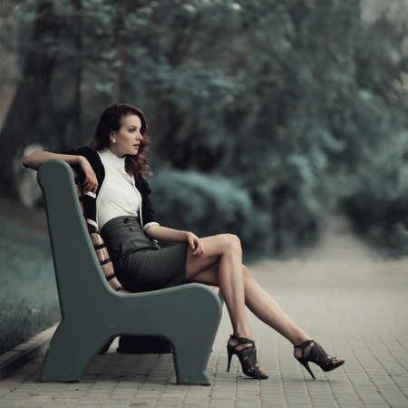 um jovem mulher só: bela jovem sentada no banco no parque