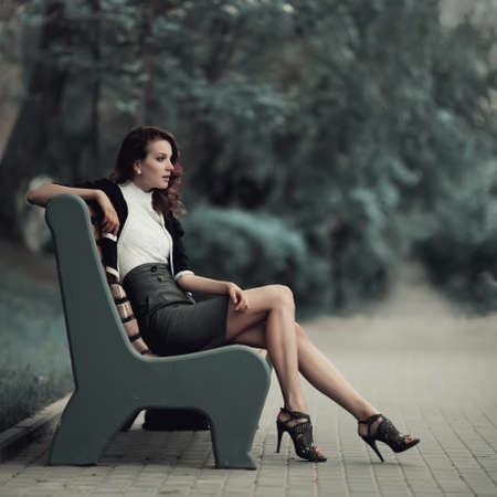 young beautiful girl sitting on bench in park photo
