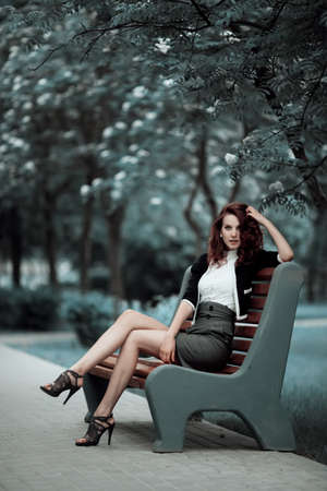 young beautiful girl sitting on bench in park