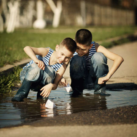 two little boys playing with paper boats in puddle photo