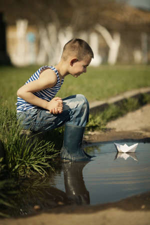 little happy boy plays with paper boats in puddle photo