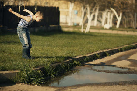 little happy boy standing in puddle photo