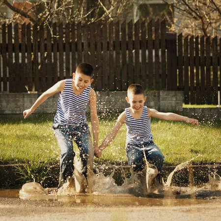 水たまりに立って小さな幸せな男の子 写真素材