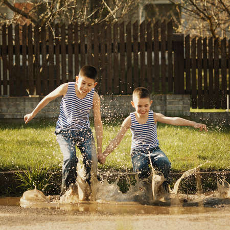 little happy boy standing in puddle Stockfoto