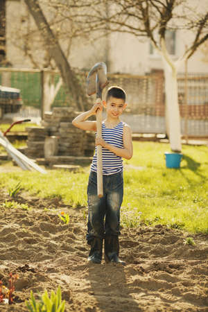 little happy boy working with shovel in garden Stock Photo - 20933455