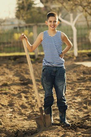 little happy boy working with shovel in garden photo