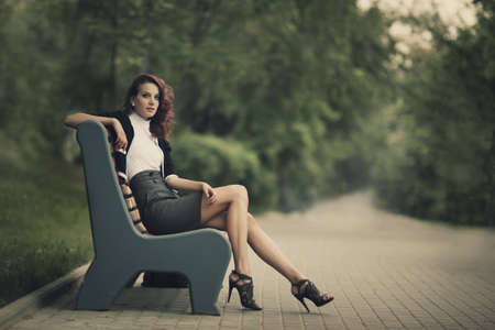street fashion: young beautiful girl sitting on bench in park