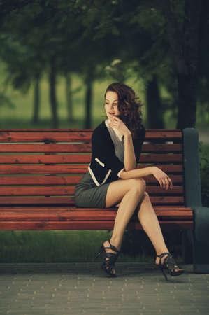 giovane bella ragazza seduta sulla panchina nel parco Archivio Fotografico