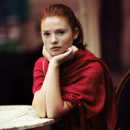 beautiful girl waiting at a table in a cafe photo