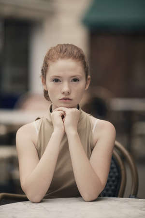 beautiful red haired girl waiting at table in cafe photo