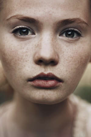 portrait of a beautiful red haired girl with freckles