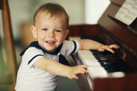 musically: little funny boy plays piano Stock Photo