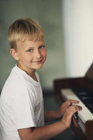 少し面白い少年再生ピアノ 写真素材