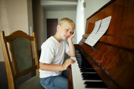 little funny boy plays piano photo