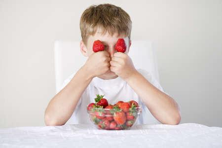 kleine grappige jongen met aardbeien Stockfoto