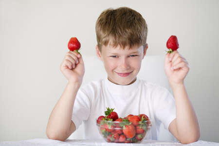 little funny boy with strawberries photo