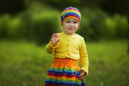 cute babies: little funny girl greets hands up Stock Photo