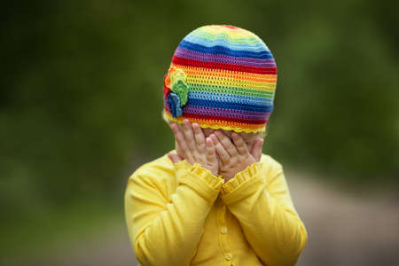 shy girl: little girl with rainbow hat is playing hide-and-seek