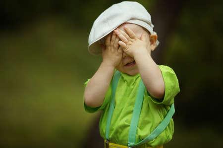 kleine lustige Junge spielt Verstecken spielen Standard-Bild