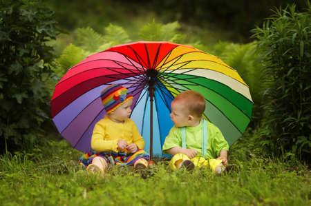 lluvia paraguas: Hijitos lindo bajo el paraguas colorido Foto de archivo
