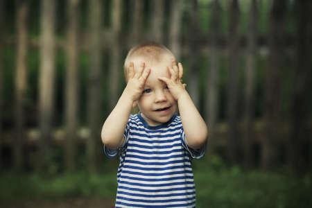 hide and seek: little boy plays hide and seek Stock Photo