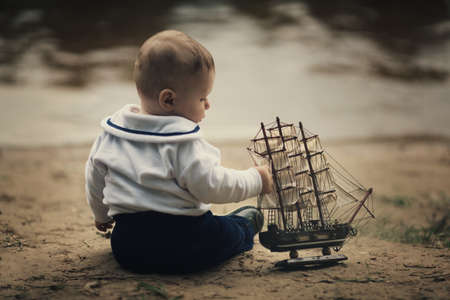 little funny boy with ship on coast of river photo