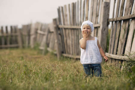 cute little girl and wooden fence photo
